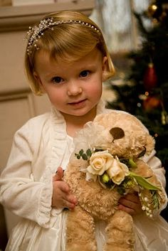 Flower girl carries her favorite doll decorated with coordinating flowers