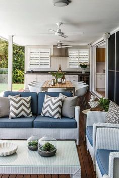 From Queensland Homes Magazine. Indoor outdoor living area. Sliding doors on to deck. Outdoor lounge and kitchen.