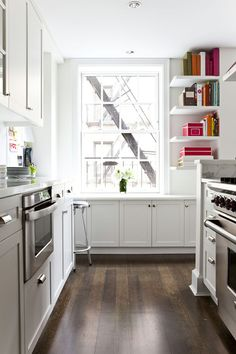 White kitchen. Colourful books. Gleaming hardwood.
