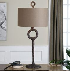 Uttermost Ferro Cast Iron Table Lamp. Hammered cast iron finished in an aged rust bronze. The round hardback drum shade is a rust beige linen fabric.