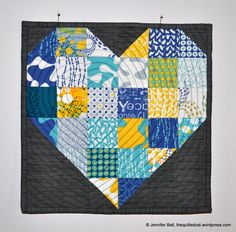 """Jennifer from The Quilted Cat is celebrating National Sewing Month with the free Color My Heart pattern from Fat Quarter Shop! """"I decided to free-motion quilt an off-centered heart shape using my Bernina USA and a dark blue Aurifil thread (#2784). I echoed quilted the small center heart using the edge of my foot so about a 1/4-inch separation between the lines."""" To see more please visit http://thequiltedcat.wordpress.com/2014/09/24/national-quilting-month-color-my-heart-quilt/"""