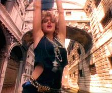 """Madonna became a fashion icon for many young women around the world and copied her """"street urchin"""" look with short skirts worn over leggings, brassieres worn as outer clothing, untidy hair, crucifix jewellery, and fishnet gloves."""