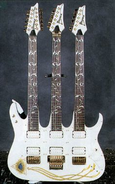 "Ibanez Jem Tripleneck Serial # LA060493 The only one of its kind. This guitar has appeared on a number of magazine covers, and can be seen on the stage during Vai's ""The Tonight Show"" performance on August 3, 1993. The first neck is a 12-string, the second neck is basically a Jem guitar set-up with a whammy bar, and the third neck is a fretless. It is stored in an insanely wide guitar case that looks like the top of a black table, and is safely stowed in Steve's home."