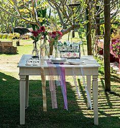 Aproveite o sol da época para fazer o almoço do primeiro dia do ano do lado de fora. Nessa mesa, o charme são as fitas e rendas. Para que não saiam voando, vale prendê-las com adesivo dupla-face