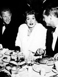 William Holden and Cary Grant face actor Jane Wyman, who looks surprised, while sitting together during a meal at an Air Force Association party, Ambassador Hotel, Hollywood, California. Photo by Murray Garrett, 1951