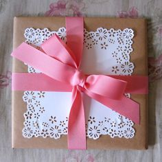 Gift Wrap Idea - Plain brown paper topped with a white paper doily and colorful ribbon / Un Chin de Magia