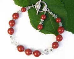 This versatile handmade bracelet features lovely red coral glass pearls, elegant crystal accents, and a convenient toggle clasp. The red coral pearls are from Swarovski (made in Austria) and have crystal glass cores to which layers of nacre have been added. Their surface has a pretty shine rather than a high gloss, and they have a comfortable weightiness. The red hue is not fire engine bright, but rather subdued, with an earthy warmth and classic quality. There are two sizes of pearls used…