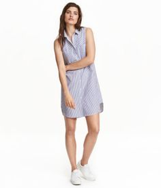 Short, sleeveless shirt dress in woven cotton fabric with buttons at front, two chest pockets, and a rounded hem. Slightly longer at back.
