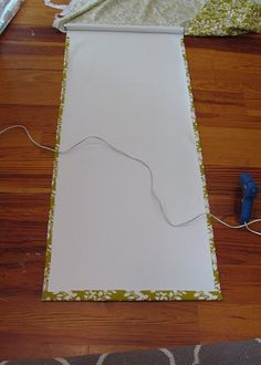 Glue fabric to a roller blind using a hot glue gun with fabric glue. Leave 1/2 inch on each side and 1 inch on the bottom. You only need as much fabric as you would see when it's unrolled in your window.