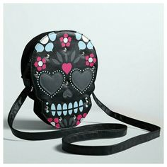 """Embellished Sugar Skull Crossbody Bag All the sweetness with no fear of a sugar crash! Black textured faux leather morphs into the shape of a calavera skull, outfitted with baby blue, hot pink, and metallic floral designs. Heart patch eyes and silver tone studs lend a punkish feel. Adjustable strap.  7"""" X 9.5"""" Strap length: 48"""" Man-made materials Imported torrid Bags Crossbody Bags"""