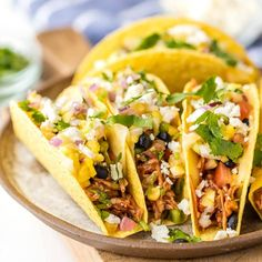 Slow Cooker Honey BBQ Chicken Tacos are an easy family dinner recipe! Topped with mango salsa, cilantro, black beans, and cheese.Perfect BBQ Chicken Tacos!