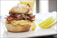 A breakfast sandwich with rich scrambled eggs, bacon, caramelized shallots, cheddar cheese, and apple.