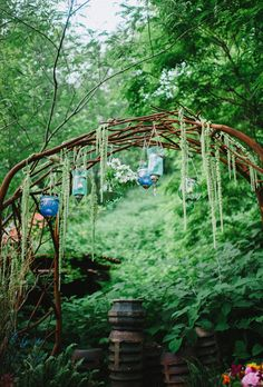 Brides.com: This Week's Best Wedding Ideas: February, 7 2014.  A nest-like iron structure hung with blue vases holding candles and clusters of white clematis serves as a ceremonial arch. Strands of amaranth give the iron branches a more organic look worthy of a garden wedding.   See more photos from this vibrant, bohemian Pittsburgh, Pennsylvania styled wedding shoot here.