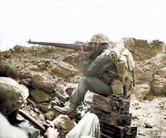 An American Marine aiming his Garand M1 rifle, whilst perched on Japanese ammunition crates on the Island of Iwo Jima,