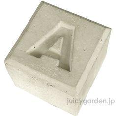 エントランスの可愛らしいオブジェにどうぞ。正方形の打ちっ放しのコンクリートにビビットなカラーの文字が入ったコンクリートブロックです。