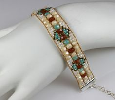 An outfit is never complete without some finishing touches and this beaded boho bracelet will top off just about any outfit. Beautifully hand-crafted from quality materials, this bohemian style bracelet is sure to be noticed and stand the test of time.   A medley of decadent cream and turquoise fire polished crystals and Japanese seed beads composes this boho loomed bracelet. The diamond geometric design give a wonderful eye-catching and color popping statement. Adjustable silver lobster…