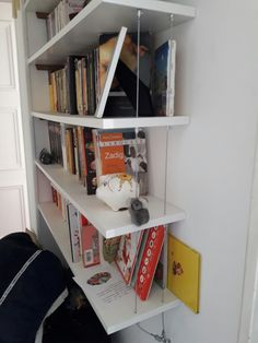 Petite bibliothèque suspendue avec filin d'acier.
