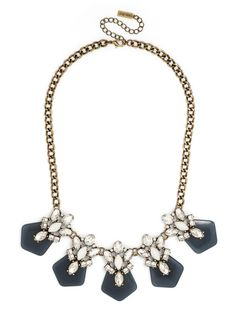 Navy gemstones crowned in icy crystal work are the stars of this graphic statement necklace—the square-cut gems add a little geometry into the eye-catching collar.
