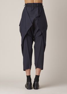 Cropped and tapered trousers in navy polyester. Pleated waistband with belt loops. Angular creased detailing creates an origami effect. Hand wash cold and lay flat to dry.