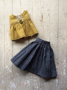 The pretty skirt is made from a lovely indigo blue cotton. It fastens with a snap at the back and comes with a pretty ochre babydoll top with