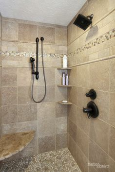 Travertine tile shower with 'Java Tan' pebble tile floor and glass tile accent. Delta faucets.