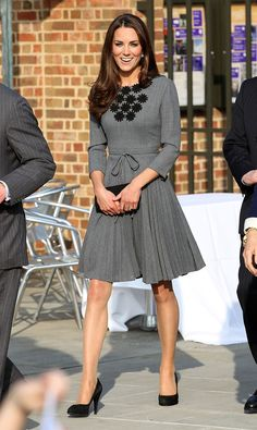 Kate looks charming in her gray dress with dark gray high heels.