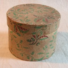 Measuring 5 inches in diameter by 3 ½ inches high, this box is ion excellent condition. The exterior paper is a fabulous hand-blocked print of oak leaves and acorns in an apple green and burgundy on a beige ground. The interior paper is simply a plain off-white paper that has aged to tan over time.