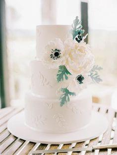 Simple three tiered white wedding cake with beautiful sugar flowers