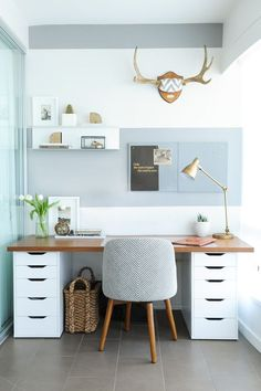 Small home office with gray and white striped wall, wood and white desk, tile floor and patterned chair | Shift Interiors