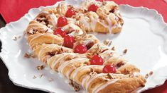 This candy cane shaped Strudel topped with pecans and cherries is a perfect dessert for Christmas.