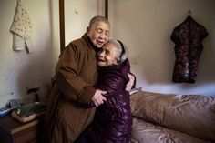 Buddhist nun Nen Qing, 81, hugs resident Luo Yudi, also 81, who has suffered a stroke. Photo by Kevin Frayer. From cbc.ca