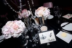 black linens with fluffy pale pink and white flowers