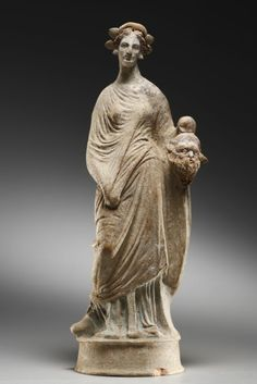 A Statuette of the Muse Thalia. H. 34.8 cm. Clay, red, pink, blue and white paint. Apulian, Canosan, 1st half of 3rd cent. B.C.