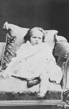 A jovem princesa Alix de Hesse está sentada em um sofá, apoiada contra uma almofada. Ela tem um xale enrolado em torno dela; usa meias curtas e sapatos. Dezembro de 1873.
