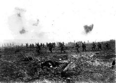 Actual combat photo taken at the time of the first assault wave on Vimy Ridge. The soldiers can be seen calmly walking behind the creeping barrage while German shells burst overhead.