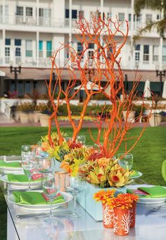 spray paint branches orange for a floral centerpiece.  instantly adds height to the table