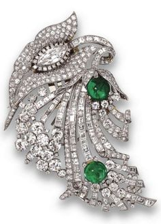 Diamond and emerald double-clip brooch, Van Cleef & Arpels, New York, circa 1935. The stylised floral and foliate motif set with a marquise-shaped diamond, completed by numerous old European-cut, round, single-cut, baguette and square-cut diamonds, accented with two round cabochon emeralds, mounted in platinum, signed Van Cleef & Arpels, N.Y., numbered. Separates into a pair of clips. #vintage #VanCleef #&Arpels #clip #brooch