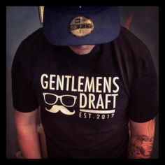 Black T-shirt.  Check out Gentlemen's Draft Clothing at https://www.facebook.com/GentlemensDraft   $2 from each item sold is donated to prostate cancer research.  Join us in  helping to fight cancer, one shirt at a time.  Stay classy like never before with our signature moustache and glasses logo on our custom designed threads.  Also check us out on:  Instagram - gentlemens_draft