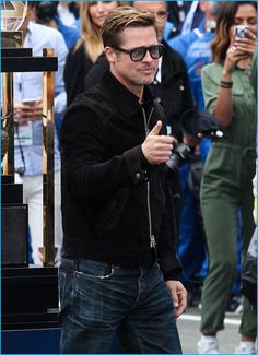 June 2016: Brad Pitt pictured at the 24 Hours of Le Mans in a suede Tom Ford jacket with the brand's Private Collection N.7 sunglasses.