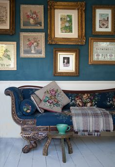picture wall, art on a dark blue background paint by Annie Sloane. White wood floors. Antique Sofa with Sanderson fabric covers and tapestry cushions.