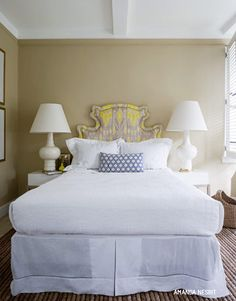 bedrooms - tan walls gray yellow ikat fabric upholstered headboard white lamps crisp white bedding bed skirt  Fun, playful bedroom with tan walls