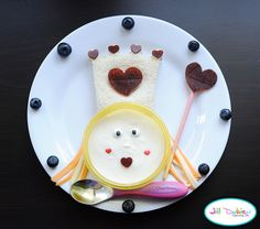 Sandwich cut into crown shape using the crown lunch punch. Fruit leather hearts. Bowl of vanilla yogurt with icing eyes, fruit leather heart mouth and heart sprinkles. Cheesestring hair. Strawberry pocky and fruit leather wand and blueberries around the plate. http://meetthedubiens.blogspot.com/2011/09/fun-food-friday-queen-of-hearts.html