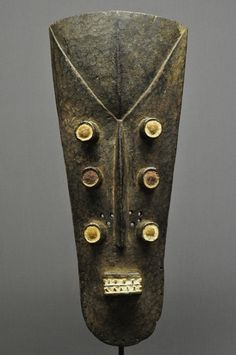 """Grebo Mask - Liberia -   This Grebo mask is carved wood with white pigment and slight traces of red pigment. It has 6 tubular eyes and has been mounted on a custom iron stand for display. The mask is 22"""" long and the overall height on stand is 35""""."""