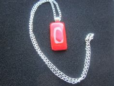 Necklace in fused glass, red and white  £8.75  This pendant was made in Lancashire using three pieces of bullseye glass fused together in a kiln. The pendant measures approx 4cms long by 2 cms across. The pendant has a silver plated bail on to a sterling silver chain.   Designed by Rachel in Lancashire, January 2015