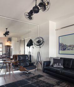 parede cinza, sofá preto e espelho na sala de estar.