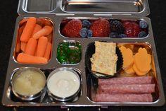 Carrots, Applesauce, Vanilla Yogurt, Wheat Thins, German Salami, pawprint cut cheese, strawberries, blueberries, blackberries & two gummy candies for a treat!  #lunchbox #planetbox #landonslunches