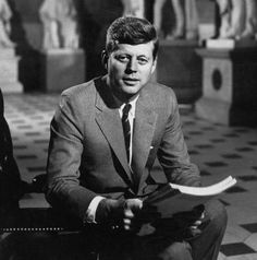 Senator John F. Kennedy seated in museum with statues, 1957