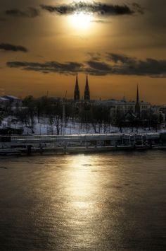 Sun setting between church steeples in Helsinki.
