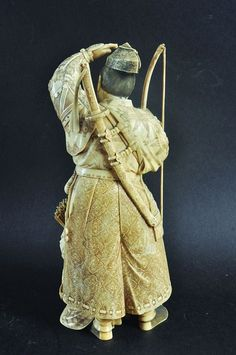 AN EXTREMELY FINE QUALITY 19TH CENTURY SIGNED JAPANESE IVORY CARVING OF A SAMURAI ARCHER, with his kneeling boy attendant, the robes of each with finely detailed engraving, the base with an engraved signature, 12.25in high.