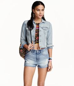 H&M LOVES COACHELLA. Short jacket in washed denim with heavily distressed details, chest pockets with flap and button, and a cut-off, raw-edge hem.
